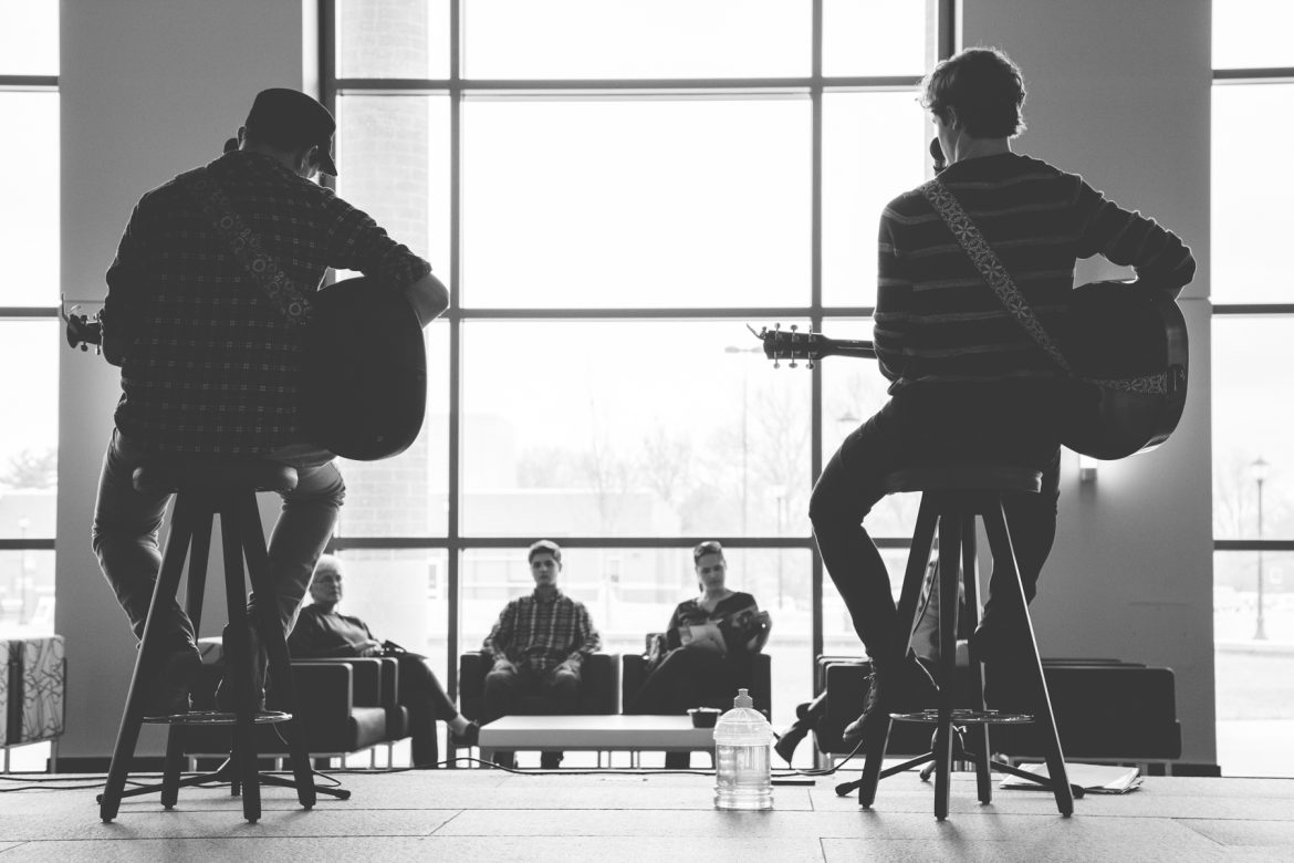 Greyscale photo of two singer-songwriters performing in the MTSU Admissions Center