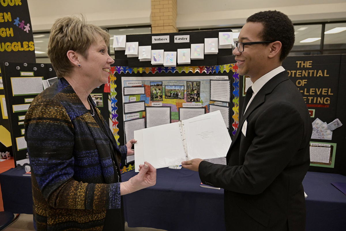Principal Leisa Justus, left, talks to Blackman High School senior Aubrey Caster and his volunteerism capstone project as part of the Blackman Collegiate Academy March 4 in the school's cafeteria. Caster plans to attend MTSU, which has partnered with Blackman in continuing the academy, and plans to study business and marketing in the Jones College of Business. (MTSU photo by Andy Heidt)
