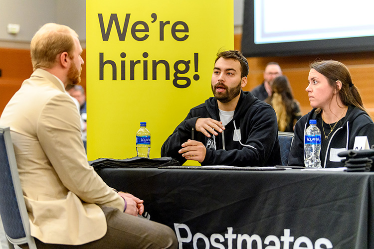 MTSU student Jeremy Noe, left, speaks with Postmates representative Pablo Hernandez and Amy Drinkwater during the Business Exchange for Student Talent, or BEST, Career Fair held Wednesday, March 20, in the Student Union Building ballroom. (MTSU photo by J. Intintoli)