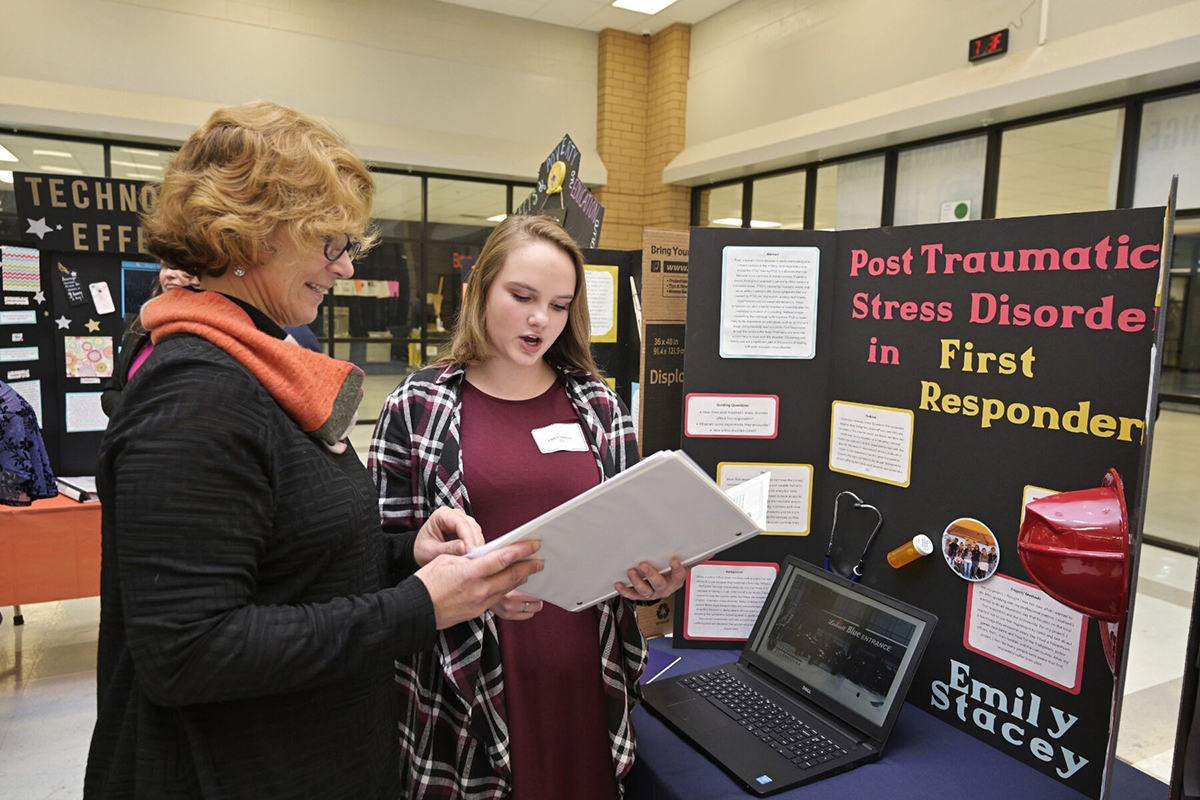 "Blackman High School chemistry and physics teacher Kim Baumann, left, listens as senior Emily Stacey shares details about her ""PTSD in First Responders"" capstone research project March 4 in the school's cafeteria. Stacey said she plans to attend MTSU and major in counseling and minor in psychology. (MTSU photo by Andy Heidt)"
