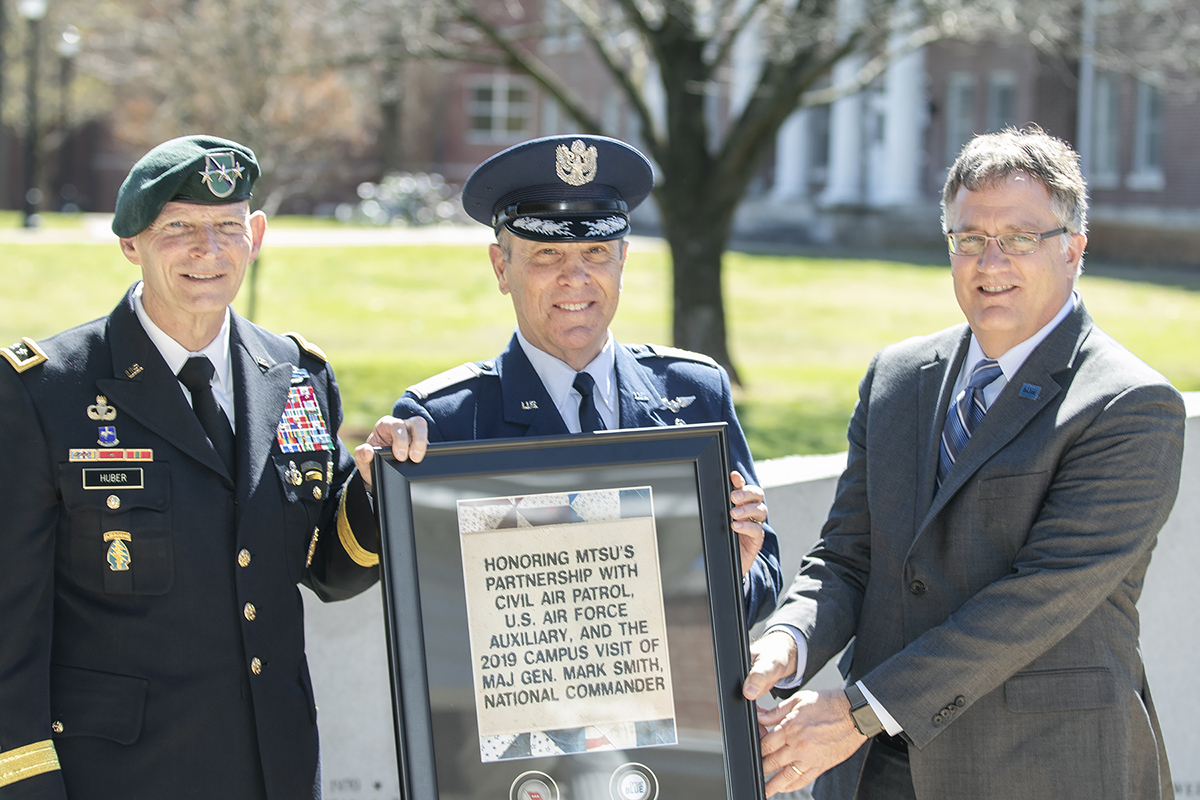 MTSU's Keith M. Huber, left, Civil Air Patrol national commander Maj. Gen. Mark Smith and MTSU Provost hold a commemorative plaque presented to Smith honoring the partnership between the university and the CAP. The event was held Friday (March 22) at the MTSU Veterans Memorial outside the Tom H. Jackson Building.