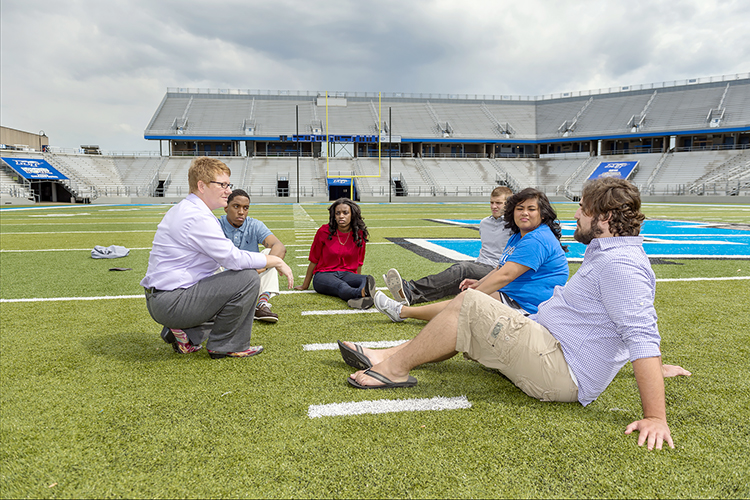 Dr. Joey Gray, far left, talks with students on the field at MTSU's Floyd Stadium during the spring 2015 semester. Gray is an associate professor in MTSU's Sports, Leisure and Tourism Studies Program. Students shown include, from bottom right, Connor Fite, Tara Fleming, JT Farmer, Takyra Wright and Requavius Macon. (MTSU photo by J. Intintoli)