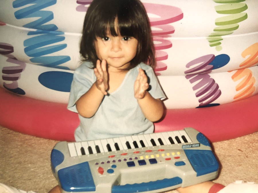 Childhood photo of Trianne Newbrey, a Public Relations major, playing a small, toy piano
