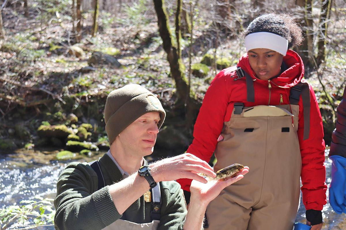 "As MTSU student Infiniti Bristol, right, observes, supervisory fisheries biologist Caleb Abramson teaches the ""SmokyMtnU"" class about the hogsucker, one of nine different species of fish our students caught in a Great Smoky Mountains National Park stream March 6. (Submitted photo by Ashley Morris)"