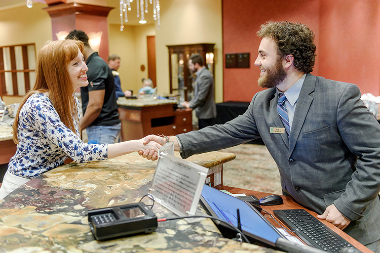MTSU student Will Mitchell, right, greets a colleague inside Embassy Suites Murfreesboro in this promotional photo for the university's new Tourism and Hospitality Management Bachelor of Science Degree Program, the only college degree track of its kind in Middle Tennessee. Mitchell also works at the hotel. MTSU's program launches in fall 2019. (MTSU photo by Eric Sutton)