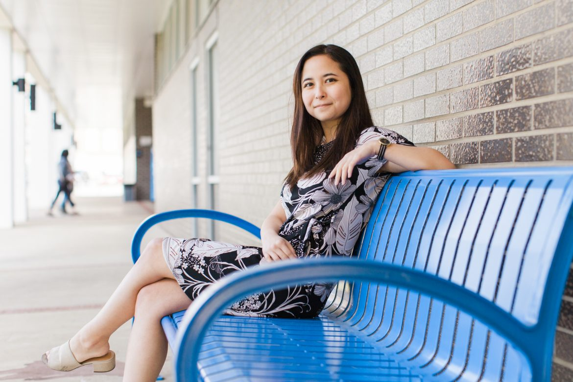 MTSU Music Business major Trianne Newbrey sitting on a blue bench outside of Peck Hall. Photo by John Goodwin