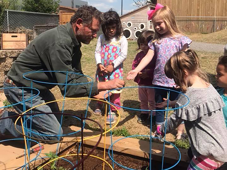 "Local entertainer, farmer and dad ""Cowboy Dan,"" left, helps children at MTSU's Ann Campbell Early Learning Center check on their vegetables in the raised garden beds at the center's wheelchair-accessible natural playground in this summer 2018 file photo. The playground at the center's North Baird Lane headquarters has been the beneficiary of funds raised at the annual ""Saddle Up"" party and fundraiser, set this year for Saturday, April 20, in the Tennessee Livestock Center. For more information, visit http://www.mtsu.edu/acelearningcenter or http://www.mtalumni.com/saddleup, or call 615-898-2458. (MTSU photo by Jacob Smith/Ann Campbell Early Learning Center)"