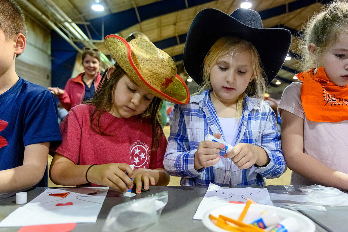 Lascassas Elementary School first-graders Kinlee McDowell, left, and Adelynn Harring, both 7, join others in making an agricultural craft Tuesday (April 16) during the MTSU Ag Education Spring Fling in the Tennessee Livestock Center. Nearly 800 youngsters learned about life on a farm. (MTSU photo by J. Intintoli)