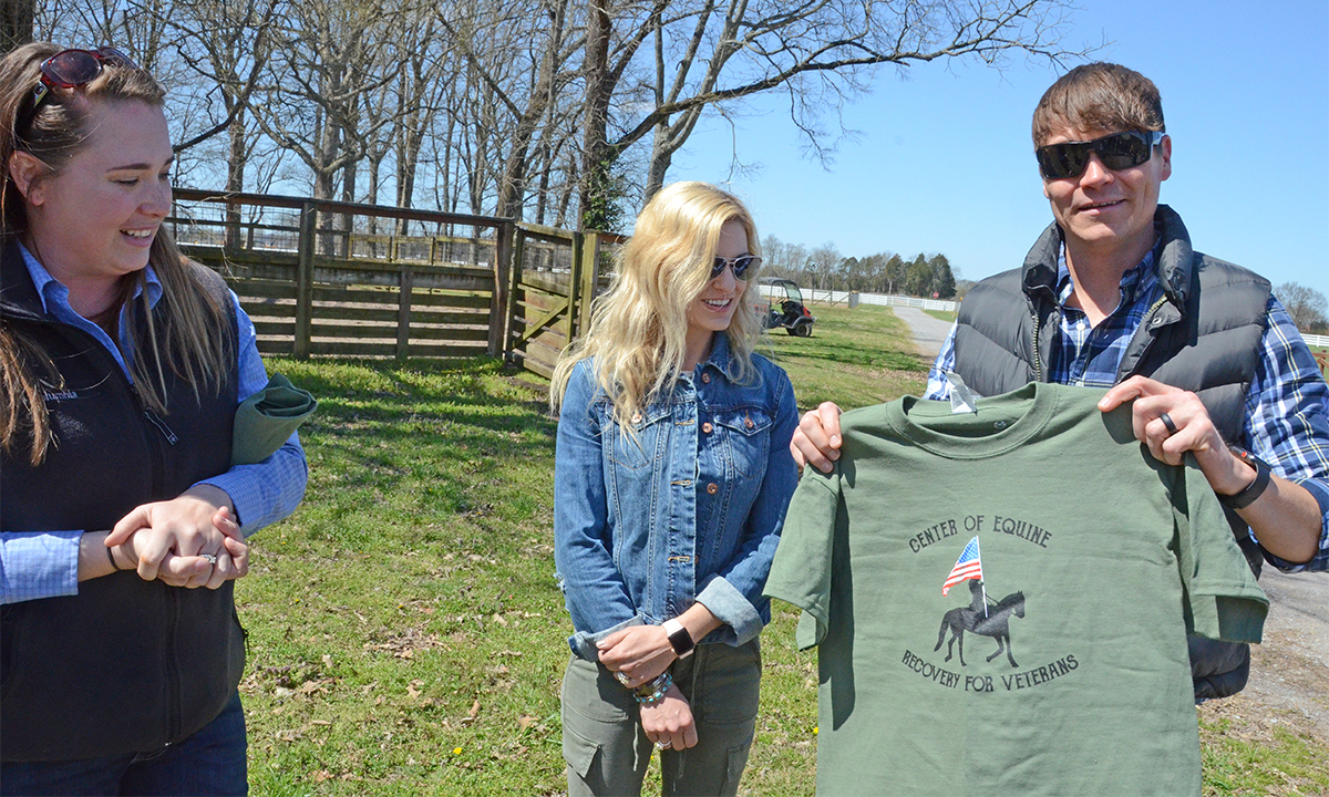 Andrea Rego, left, an MTSU horse science instructor and coordinator of the Center of Equine Recovery for Veterans program to assist with equine therapy for veterans, presents Brad Arnold with a CERV T-shirt as his wife, Jen Arnold, watches outside the Horse Science Center on West Thompson Lane. The Arnolds delivered a $15,000 check for the equine therapy center from the rock band 3 Doors Down's Better Life Foundation.