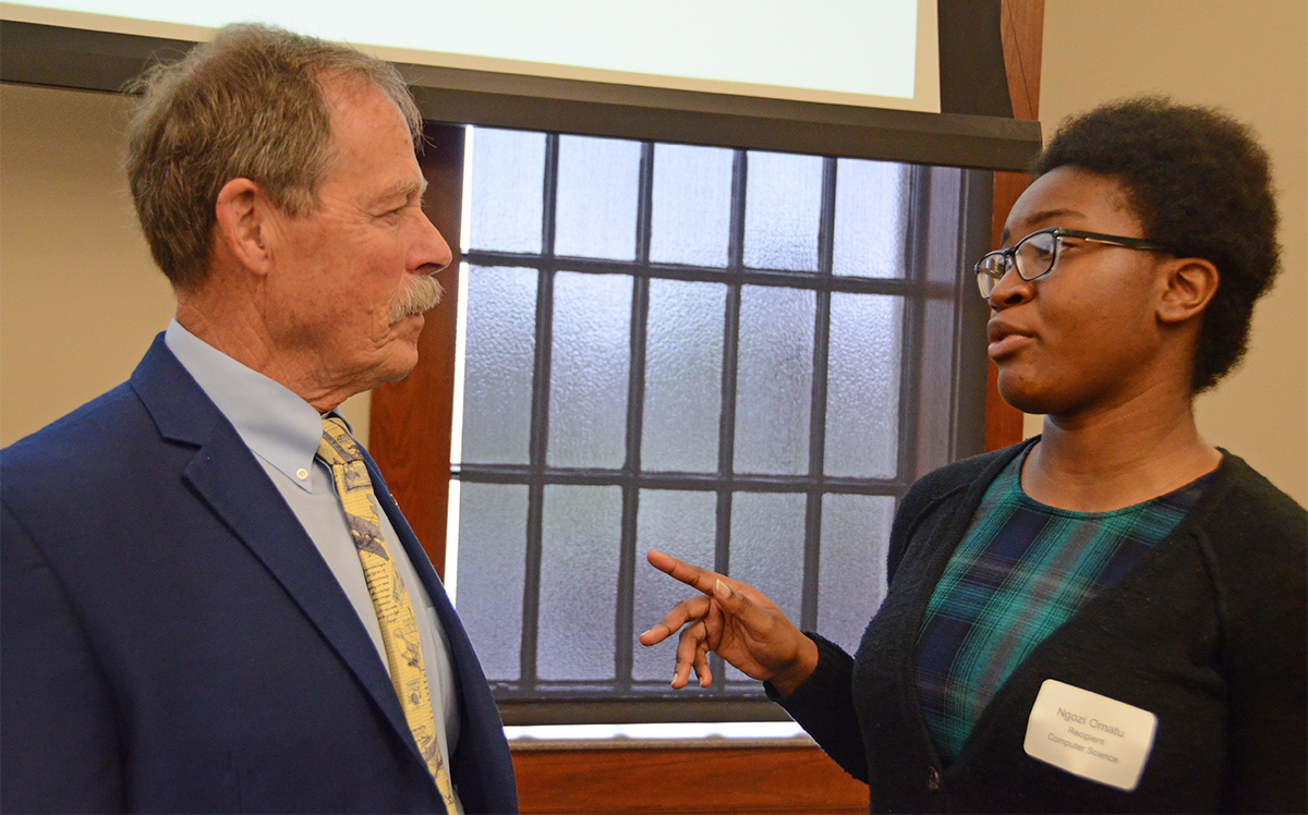 "Retired NASA astronaut Robert ""Hoot"" Gibson, left, of Murfreesboro listens as Ngozi Omatu, an MTSU senior computer science major, shares about her research experience. They talked before a luncheon to recognize undergraduate research at MTSU. Gibson was the keynote speaker."