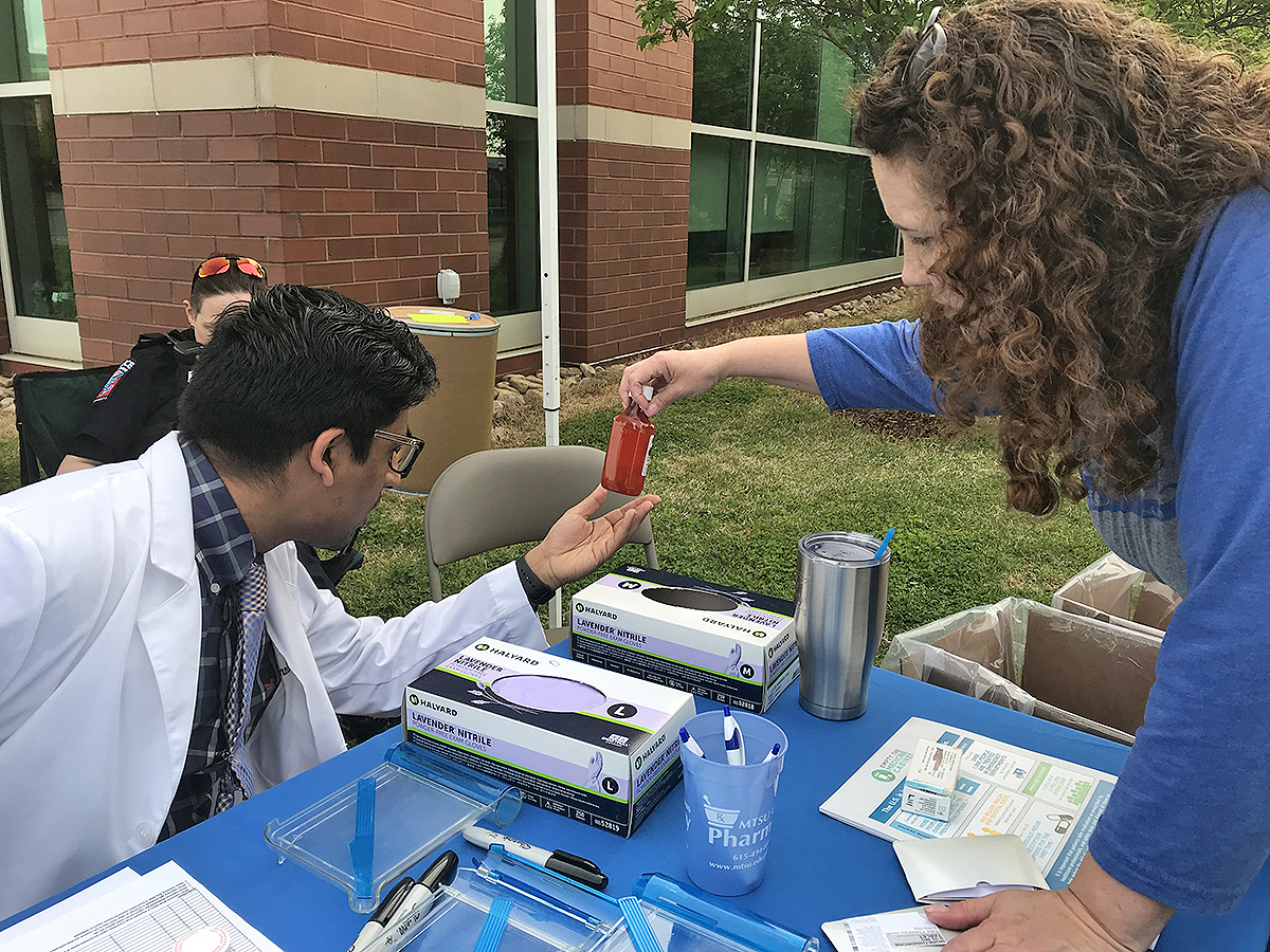 Lipscomb University College of Pharmacy second-year student Chintan Patel, left, and MTSU Campus Pharmacy pharmacist Tabby Ragland inspect the quantity of the medicine left inside the bottle dropped off Tuesday, April 23, during the MTSU Prescription Drug Take-Back Day. They collected more than 51 pounds of unwanted medications by the end of the event.