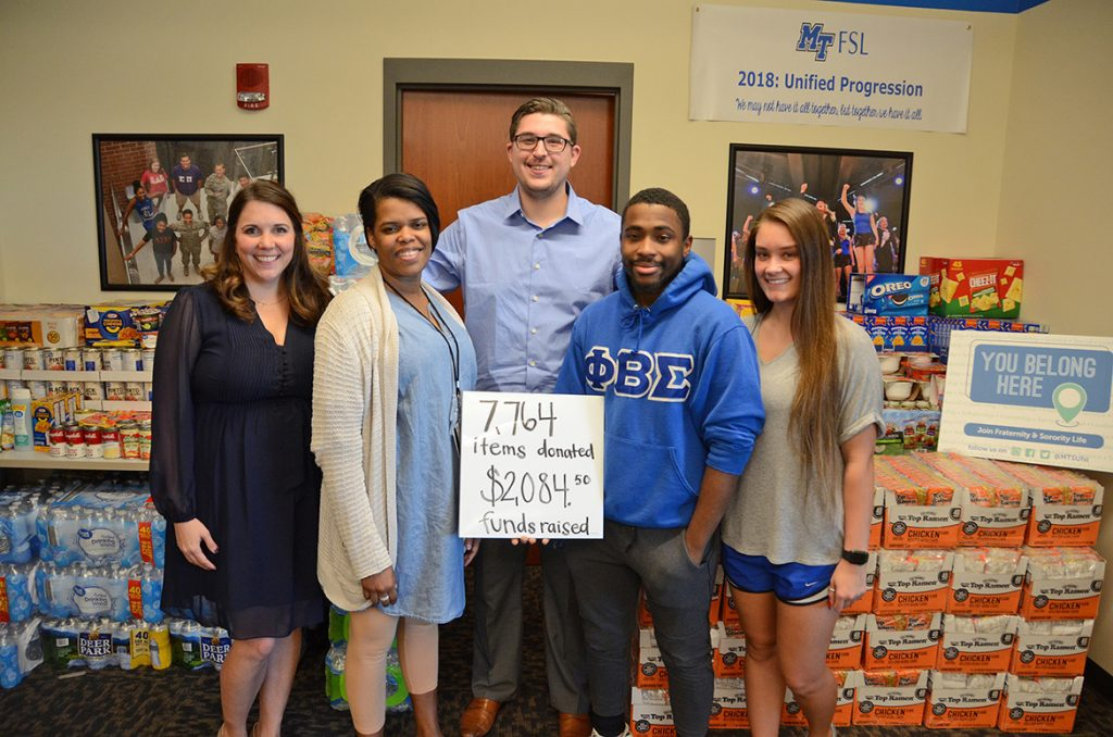 Representatives of the MTSU Greek Week committee, MTSU Fraternity and Sorority Life, and the Student Food Pantry stand in front of the thousands of donated nonperishable food items collected during the recent Greek Week food drive to replenish the pantry. Pictured, from left, outside FSL's Student Union offices, are FSL Director Leslie Merritt; Danielle Rochelle, MT One Stop outreach coordinator who oversees the Student Food Pantry; Jordan Borchert, FSL coordinator; junior Deshaun Covington of Phi Beta Sigma fraternity and Greek Week committee member; and senior Alex Revor, member of Chi Omega sorority and Greek Week committee chair. As noted by the sign, the food drive collected 7,764 items and $2,084.50 in funds. (MTSU photo by Jimmy Hart)