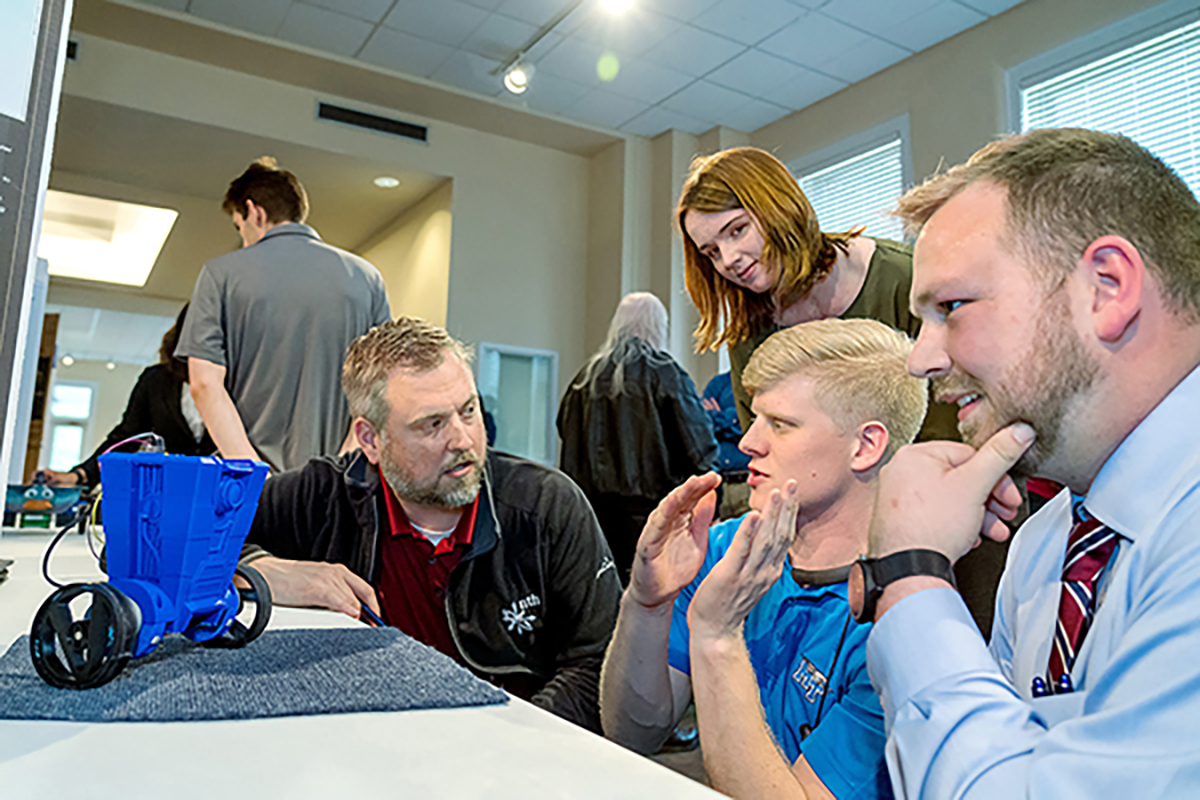 MTSU Engineering Technology Open House senior projects judge Jeff Buck, kneeling left, of Automation Nth listens to Elijah Little, center, Sean Daily and Kelly Maynard, rear, talk about the CL4P-TP self-balancing robot on wheels and how it operates.
