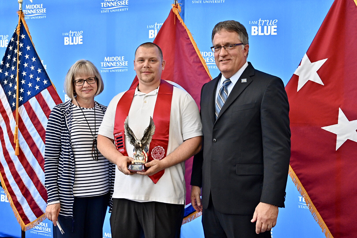 MTSU graduating student veteran Derrick Jones, second from left, accepts the Veteran Leadership Award from Deb Sells, left, vice president of Student Affairs, and Provost Mark Byrnes Wednesday, April 24, during the Graduating Veterans Stole Ceremony at the Miller Education Center. Jones has been a student worker in the Daniels Veterans Center.