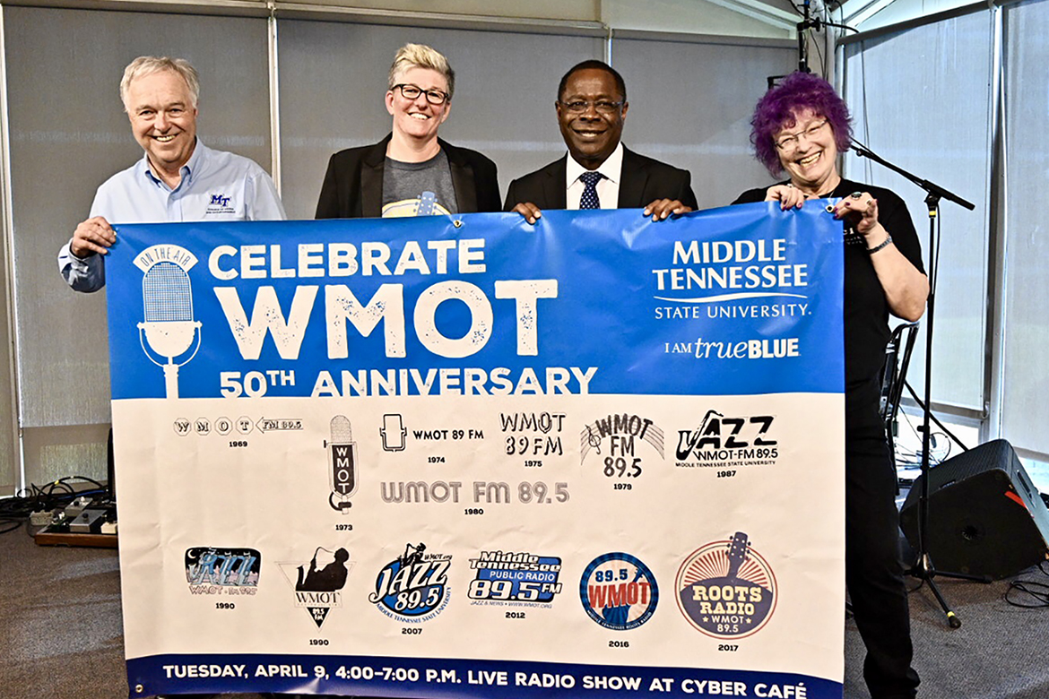 Ken Paulson, left, dean of MTSU's College of Media and Entertainment, joins Val Hoeppner, executive director of WMOT Roots Radio 89.5, MTSU President Sidney A. McPhee and Jessie Scott, WMOT host, to display the 50th anniversary banner for the MTSU-owned station during a special celebration held Tuesday, April 9, at the Cyber Cafe on the Blue Raider campus. (MTSU photo by J. Intintoli)