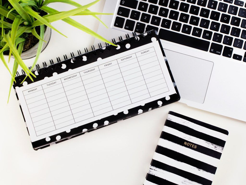Laptop, plant, and planner, and notebook on a white desk. Photo by Emma Matthews Digital Content Production on Unsplash