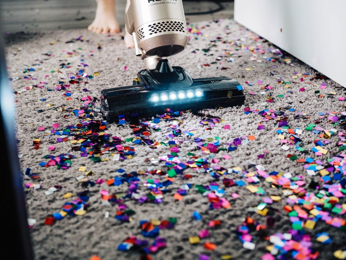 Vacuum cleaning up colorful confetti off of a carpet