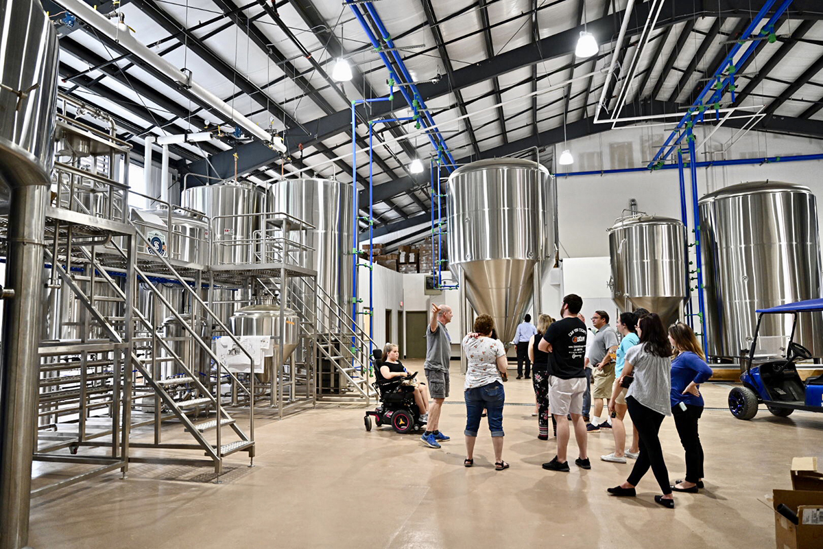 On a tour of the Hop Springs facility Thursday, May 23, visitors learn about the brew house on the left and the large fermentation and regular tanks in the room. MTSU and Hop Springs celebrated with a grand opening of the facility. (MTSU photo by J. Intintoli)