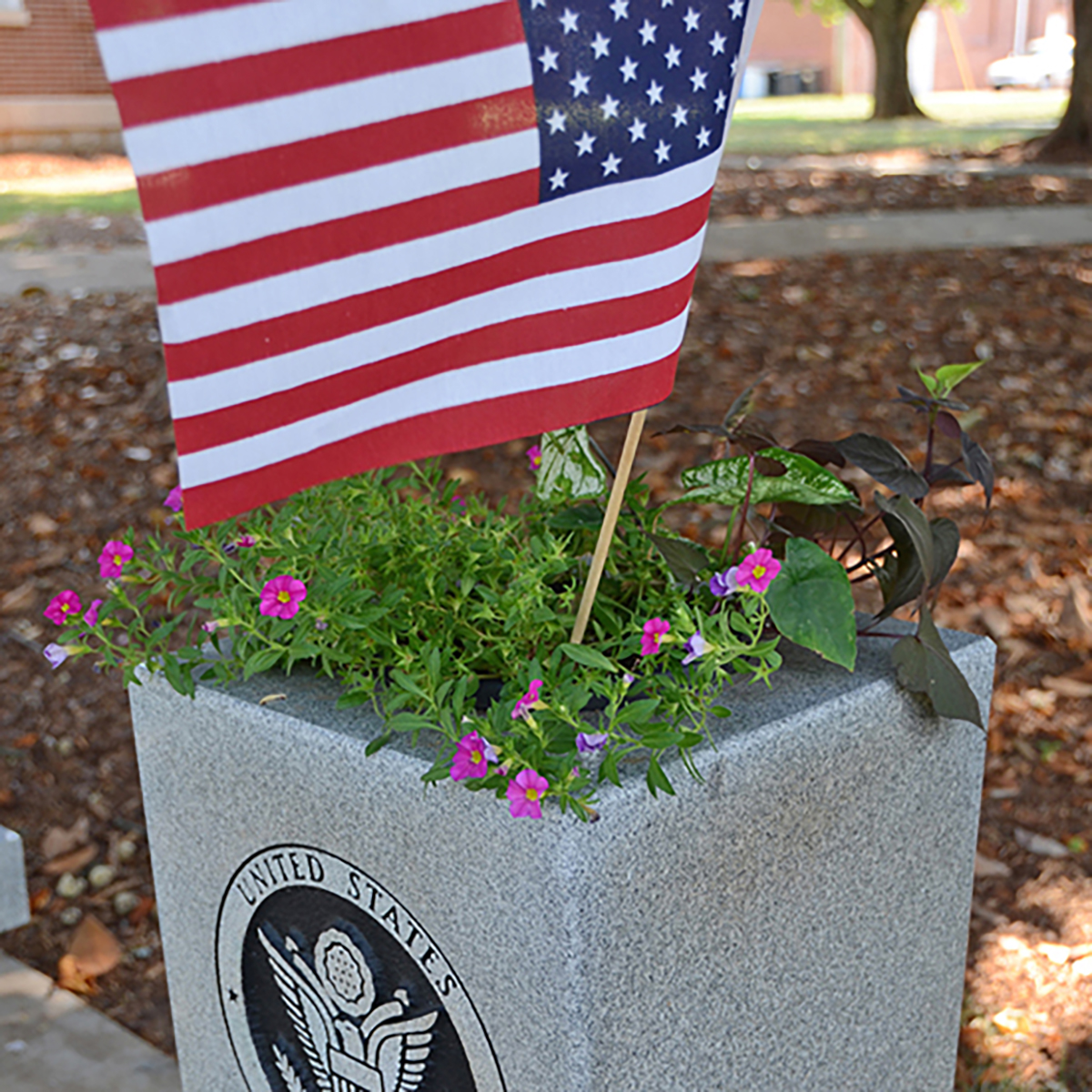 A U.S. flag sits atop flowers at the Military Memorial site outside the Tom H. Jackson Building on the MTSU campus. (MTSU file photo by Randy Weiler)