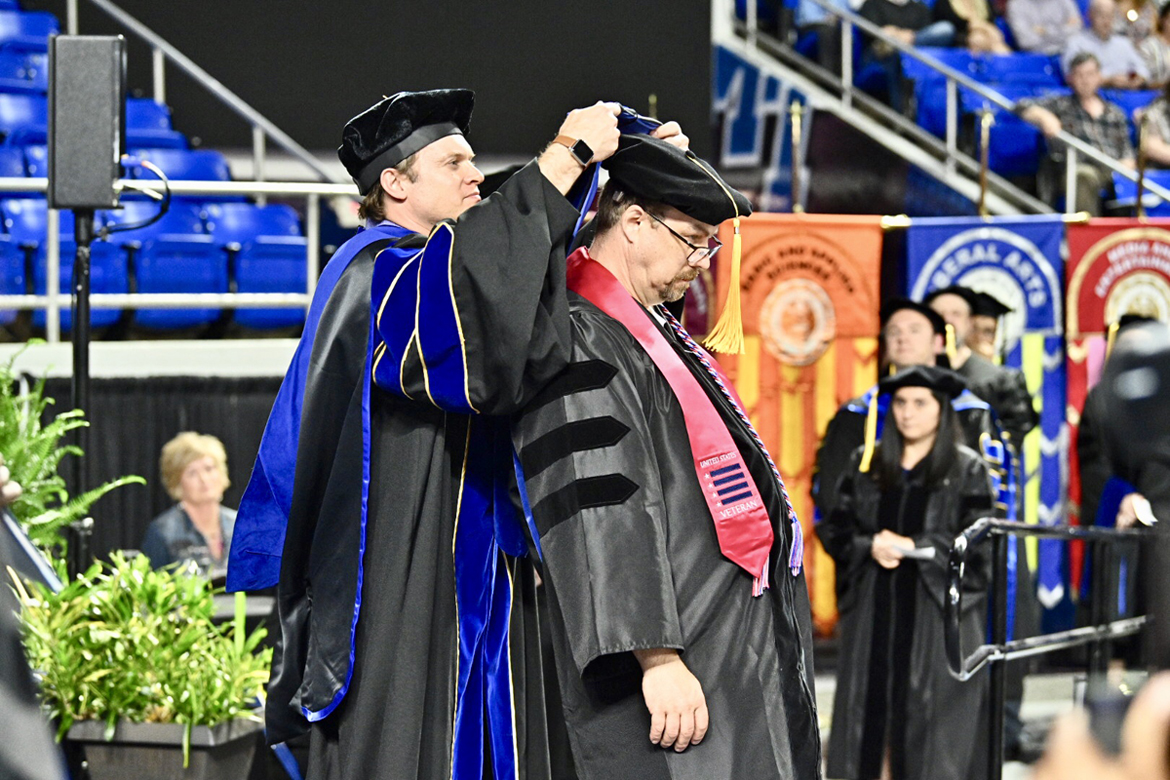 Dr. Cyrille Magne, an MTSU associate professor in literacy studies, helps MTSU graduate Perry Louden don the hood signifiying his new doctoral degree during the Friday, May 3, spring 2019 College of Graduate Studies commencement ceremony at Murphy Center. Louden, a Rutherford County Schools teacher, earned his doctorate in literacy studies, his fourth MTSU degree. MTSU awarded 384 master's and doctoral degrees in the May 3 ceremony and will present 2,145 undergraduates with their diplomas in dual ceremonies Saturday, May 4. (MTSU photo by J. Intintoli)