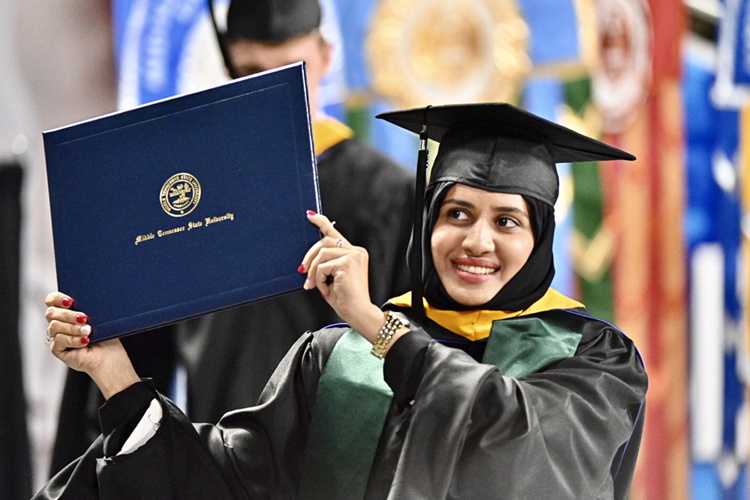 A new holder of an advanced degree from MTSU's College of Graduate Studies and the Department of Health and Human Performance displays her accomplishment to family and friends as she returns to her seat in Murphy Center Friday, May 3, during the university's spring 2019 graduate commencement ceremony. MTSU awarded 384 master's and doctoral degrees in the May 3 ceremony and will present 2,145 undergraduates with their diplomas in dual ceremonies Saturday, May 4. (MTSU photo by J. Intintoli)
