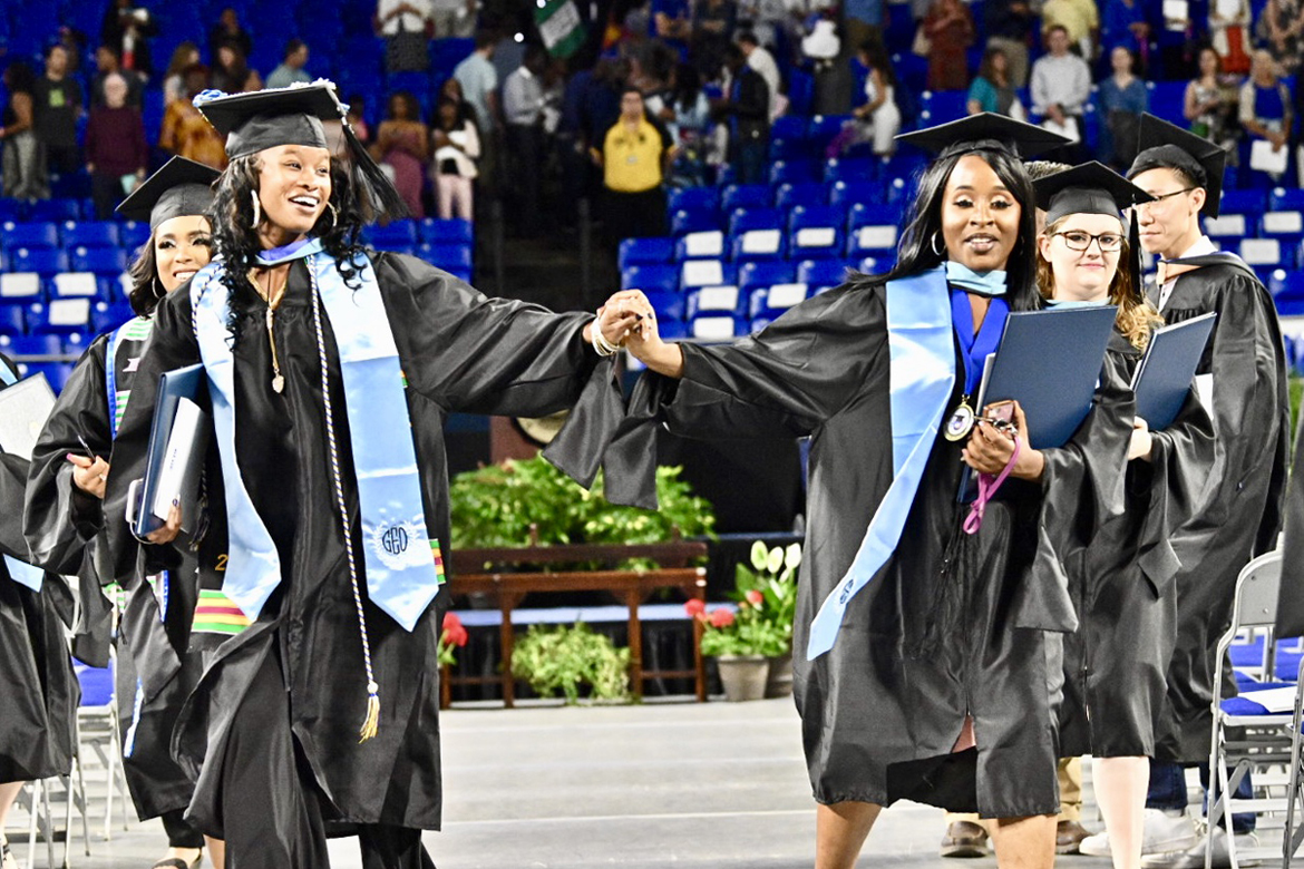 A pair of joyful spring 2019 MTSU graduates clutch their new advanced degrees in education and hold hands as they file out of Murphy Center during the university's College of Graduate Studies May 2019 commencement ceremony. MTSU will present more than 800 students with degrees in the summer 2019 commencement ceremony set Saturday, Aug. 10. (MTSU file photo by J. Intintoli)
