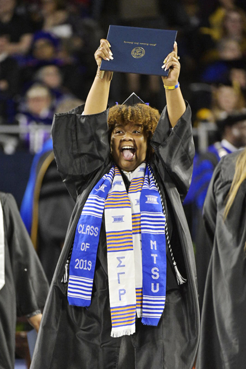 A joyful MTSU undergraduate holds her hard-won degree aloft in celebration Saturday, May 4, during the university's spring 2019 afternoon commencement ceremony at Murphy Center. MTSU presented 2,145 undergrads with their diplomas in two events Saturday and 384 graduate students with degrees May 3, bringing the university's total new alumni to 2,529. (MTSU photo by Andy Heidt)