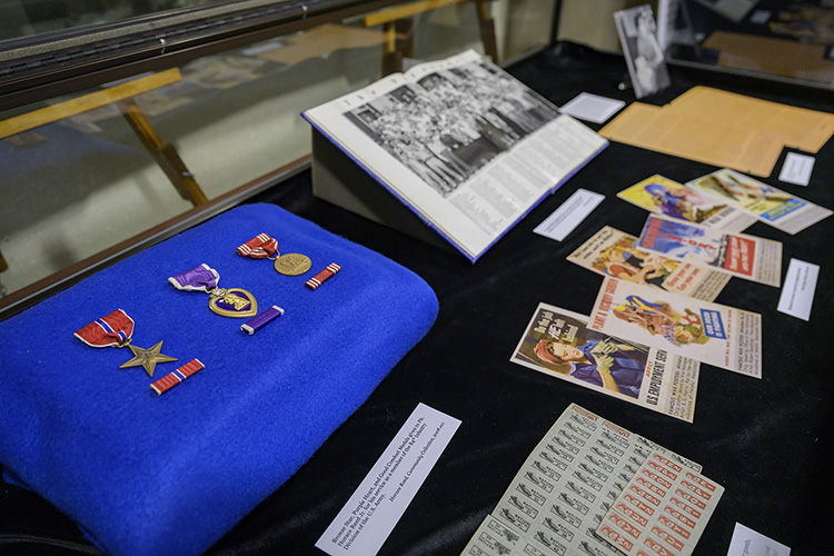 "Some of the artifacts on display in ""A Great and Noble Undertaking: Remembering Tennesseans in World War II"" at the James E. Walker Library include medals, ration stamps, wartime propaganda and a 1946 edition of the Midlander, MTSU's yearbook, with a photograph of military veterans standing in front of Kirksey Old Main. (MTSU photo by Andy Heidt)"