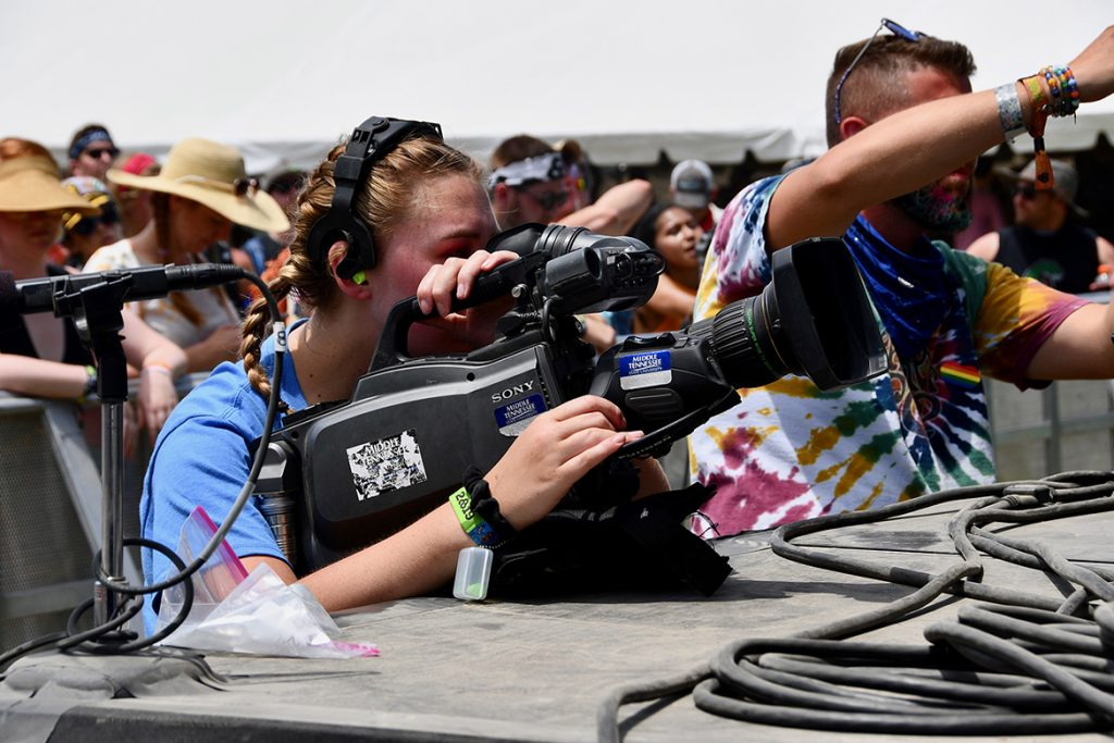 Taylor Sullivan, a music business and video production major at MTSU, gets up close to the action Sunday, June 16, while filming a concert on the Bonnaroo Who Stage in Manchester, Tenn. (MTSU photo by Andrew Oppmann)