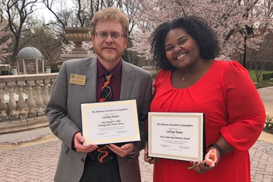 Dr. LaToya Eaves, right, an assistant professor in Global Studies and Human Geography at MTSU, and Dr. Derek Alderman, current past president of the American Association of Geographers, hold the two award certificates Eaves received at the association's luncheon earlier this spring in Washington, D.C. (Submitted photo)
