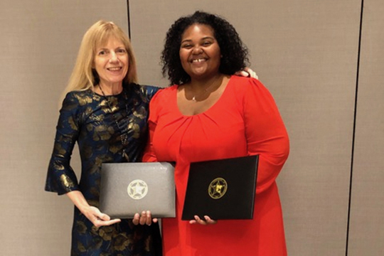 Dr. LaToya Eaves, right, an assistant professor in Global Studies and Human Geography at MTSU, is pictured with Dr. Sheryl Luzzadder-Beach, president of the American Association of Geographers, at the association's luncheon earlier this spring in Washington, D.C. Eaves holds the two award certificates she received for the Ronald F. Abler Distinguished Service Honors award and the AAG Enhancing Diversity Award. (Submitted photo)