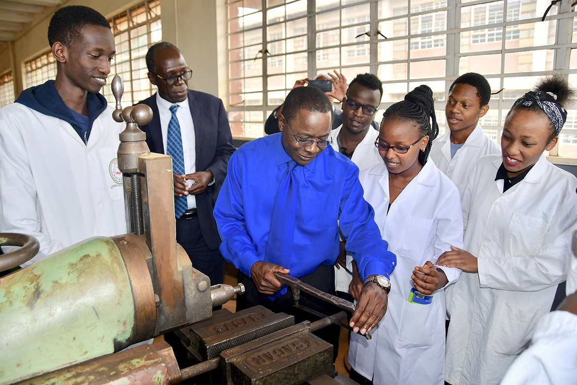 MTSU President Sidney A. McPhee works a hacksaw at an applied engineering laboratory at Moi University in Kenya as students watch. (MTSU photo by Andrew Oppmann)