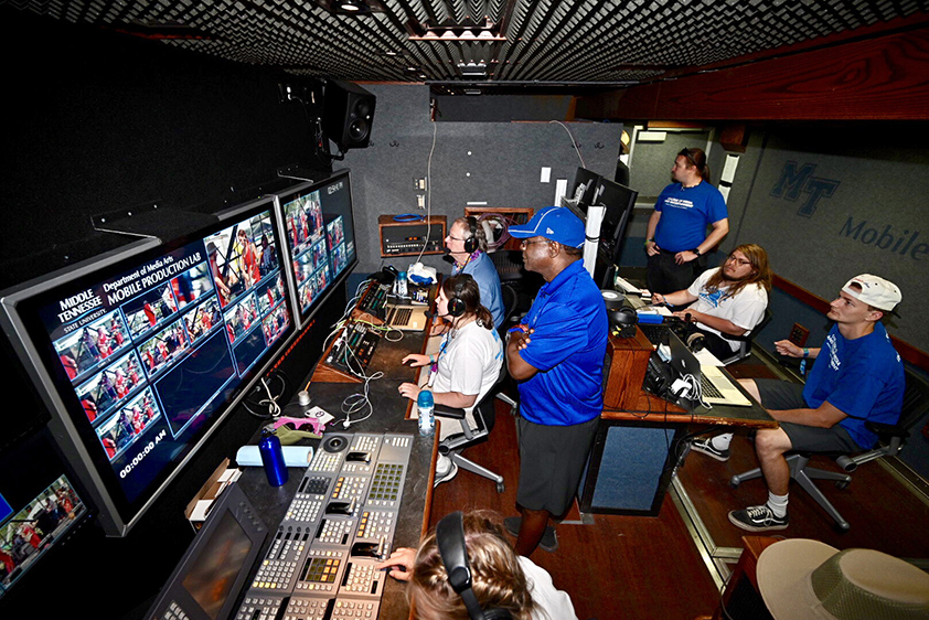 MTSU President Sidney A. McPhee, center, looks on as Media Arts students work inside the university's Mobile Production Lab on site Friday, June 14, at the Bonnaroo Music and Arts Festival in Manchester, Tenn. (MTSU photo by J. Intintoli)