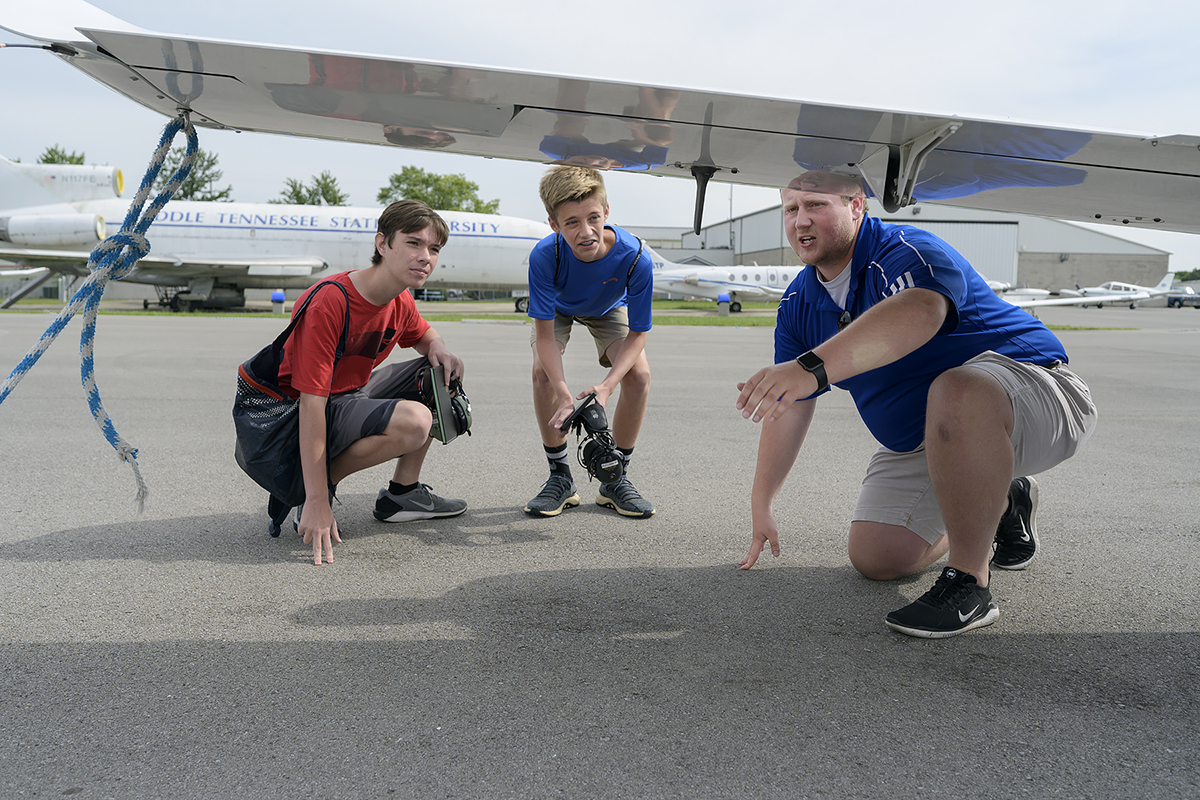 Dustin Eaves, 14, left and Rylan Smith, 15, respective freshman and sophomore at Mt. Juliet (Tenn.) High School, learn about propeller-to-wing-to- tail safety checks from MTSU student flight instructor Michael Eaton, a senior pro pilot major from Chattanooga, Tenn., as they prepare to fly during the aerospace department's Introduction to Aviation Camp June 12 at Murfreesboro Airport. (MTSU photo by Andy Heidt)