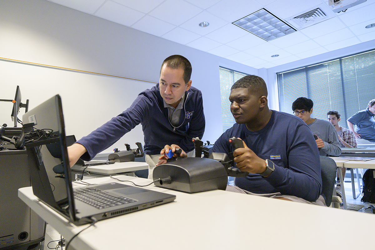 Matthew Torres, left, assistant chief flight instructor for the MTSU Flight Operations Center, suggests Jastin Jackson, 17, a rising senior at Franklin (Tenn.) High School, make an adjustment while training on a simulator during camp June 12. Jackson is a football player and member of the Franklin wrestling team. (MTSU photo by Andy Heidt)