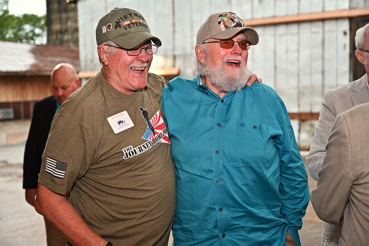 Sporting a T-shirt bearing the name of Charlie Daniels' foundation, The Journey Home Project, veteran Dennis Buchanan and Daniels share a laugh during the second Veteran Impact Celebration Thursday, June 27, at The Grove at Williamson Place. The Journey Home Project gave $100,000 to the MTSU veterans center for the second consecutive year. (MTSU photo by Andy Heidt/J. Intintoli)