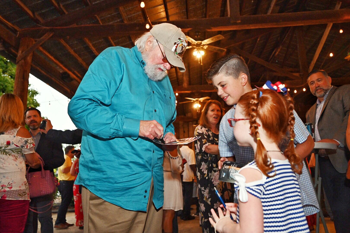 Country Music Hall of Fame member Charlie Daniels, left, signs autographs for two youngsters who attended the second Veteran Impact Celebration Thursday, June 27, at The Grove at Williamson Place. Daniels' foundation, The Journey Home Project, gave the MTSU veterans center a $100,000 gift. (MTSU photo by J. Intintoli)