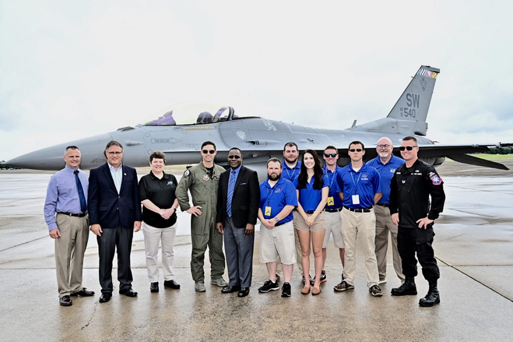 MTSU President Sidney A. McPhee, fifth from left, poses for a photo Friday at Smyrna Airport with other university faculty, staff and students as well as members of the F-16 Viper Demonstration Team, which hosted the group for the last practice before the scheduled Great Tennessee Air Show this weekend. To the left of McPhee is U.S. Air Force Maj. Garret Schmitz, commander of the Viper demo team. (MTSU photo by J. Intintoli)