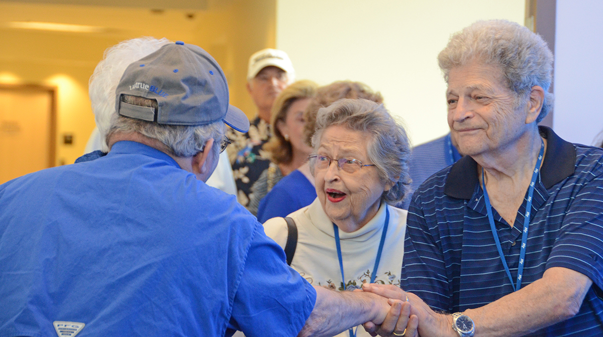 Alumni Summer College attendees Helen (Classes of 1968, '69, '70 and '72), center, and Glen ('69, '86) Emery greet fellow MTSU alumnus Joe Nunley Jr. ('69, '74) in a blue carpet setting in the Miller Education Center. Nearly 80 alumni attended the three-day event this year. (MTSU photo by Randy Weiler)