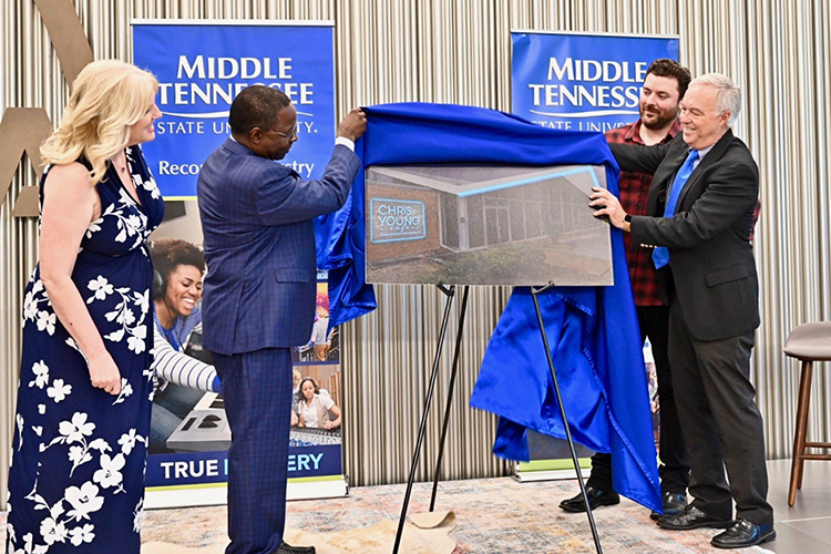 Multi-platinum country artist and former MTSU student Chris Young, shown at center right, looks on as President Sidney A. McPhee and other university officials unveil the concept rendering for the Chris Young Café, a live performance venue on the Murfreesboro university's campus. (MTSU photo by J. Intintoli)