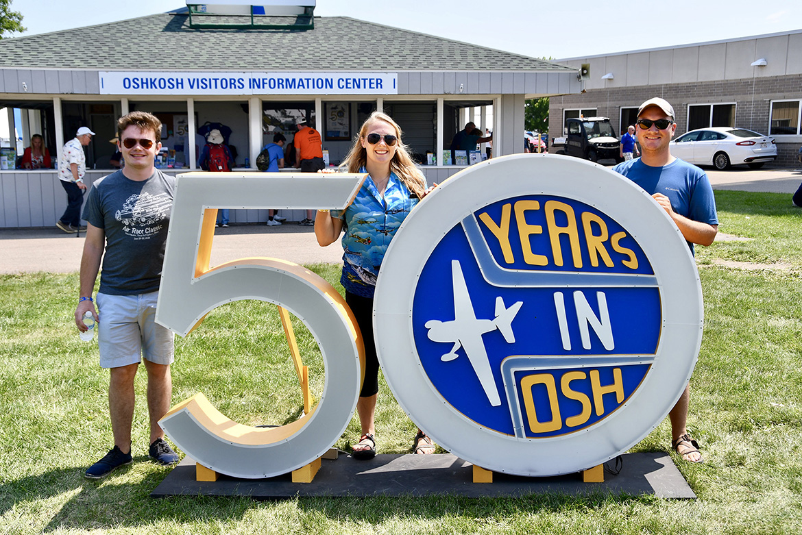 MTSU's Jackson Dalton, left, Elizabeth Keller and Charles Greenfield pose in front of a sculpture celebrating the 50th year that the EAA AirVenture event has been staged in Oshkosh, Wis. (MTSU photo by Andrew Oppmann)