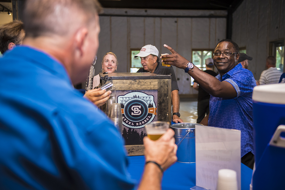 """MTSU President Sidney A. McPhee, right, raises a toast during the 2018 Pigskin Pregame event last August at university fermentation science partner Hop Springs and Steel Barrel Brewery, once again a beverage sponsor for this year's """"Pigskin"""" event. It will be held at 6 p.m. Saturday, Aug. 10, at the home of Jonathan Harmon, 746 E. Main St., in Murfreesboro. (MTSU file photo by Eric Sutton)"""