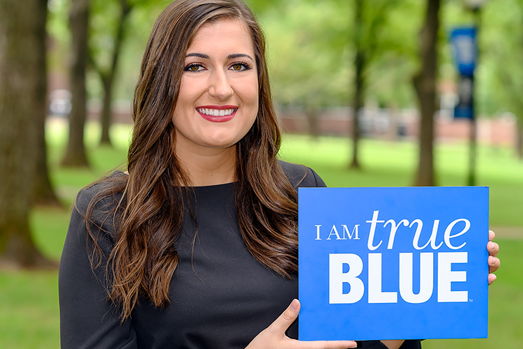 MTSU senior Delanie McDonald, the 2019-20 Student Government Association President, holds a True Blue sign in this photo taken at Walnut Grove. (MTSU photo by J. Intintoli)