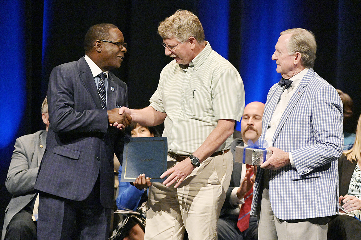 MTSU physics professor William Robertson, center, accepts the 2019 Career Achievement Award from university President Sidney A. McPhee, left, and MTSU Foundation President Ron Nichols during the annual Fall Faculty Meeting held Thursday, Aug. 22, in Tucker Theatre. (MTSU photo by Andy Heidt)