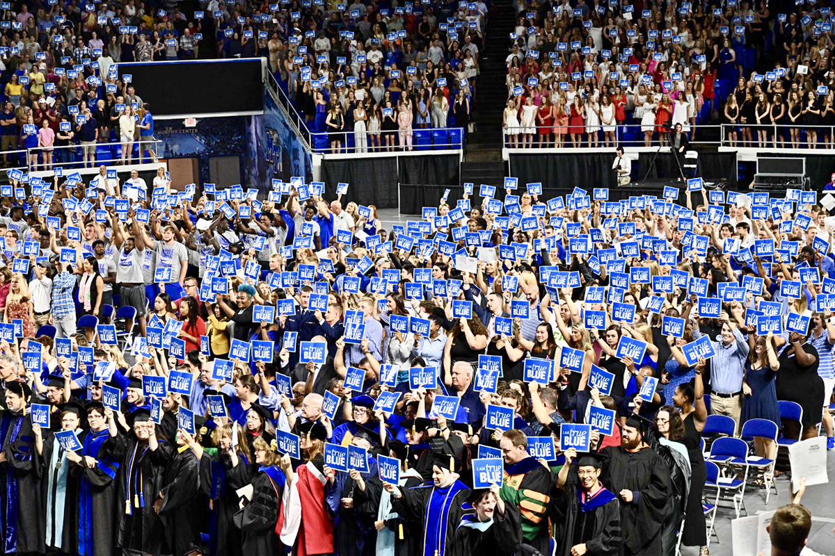 Joined by staff, faculty, student leaders and student athletes seated on the floor holding True Blue signs, the 2019 freshman class and other guests recite the True Blue Pledge as part of the University Convocation Saturday, Aug. 24, in Murphy Center. (MTSU photo by J. Intintoli)