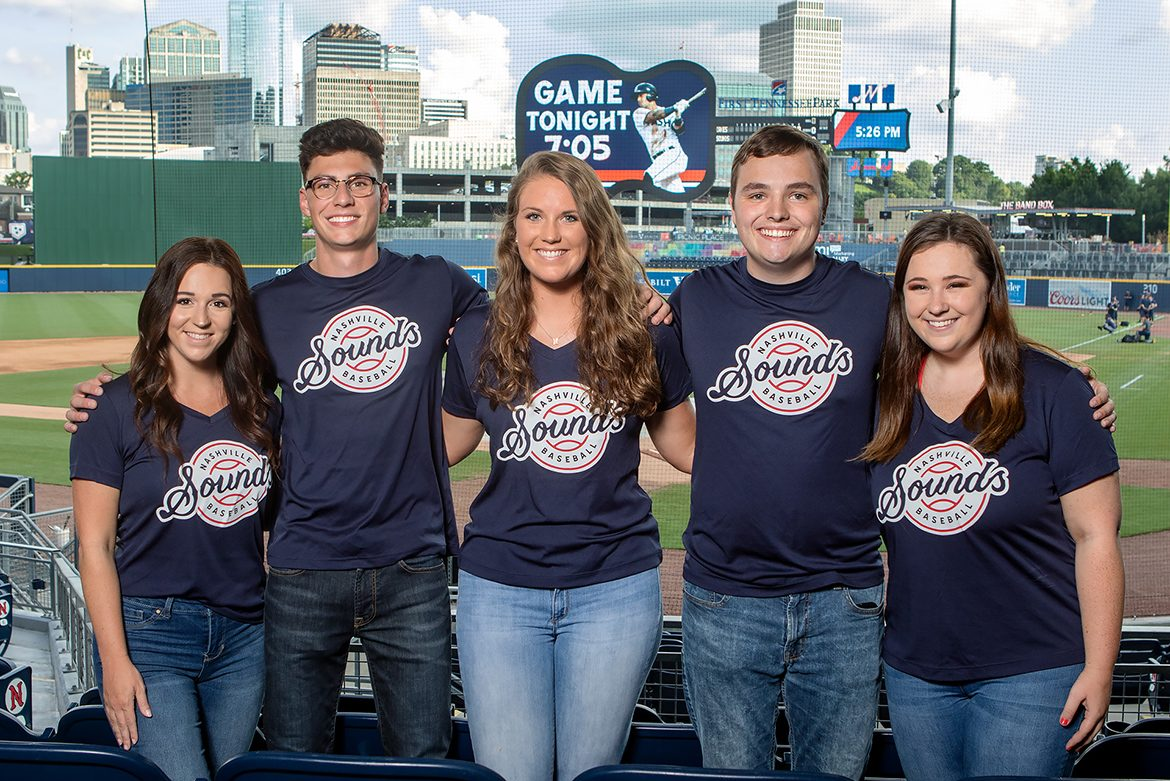 MTSU students serving as brand ambassadors for the Nashville Sounds this season pose in the stands in front of the field and scoreboard. Pictured, from left, are Emily Undieme, Cody Gentile, Mary Ruth Wheeler, Kobe Hermann and Jessie Steele. (MTSU photo by James Cessna)