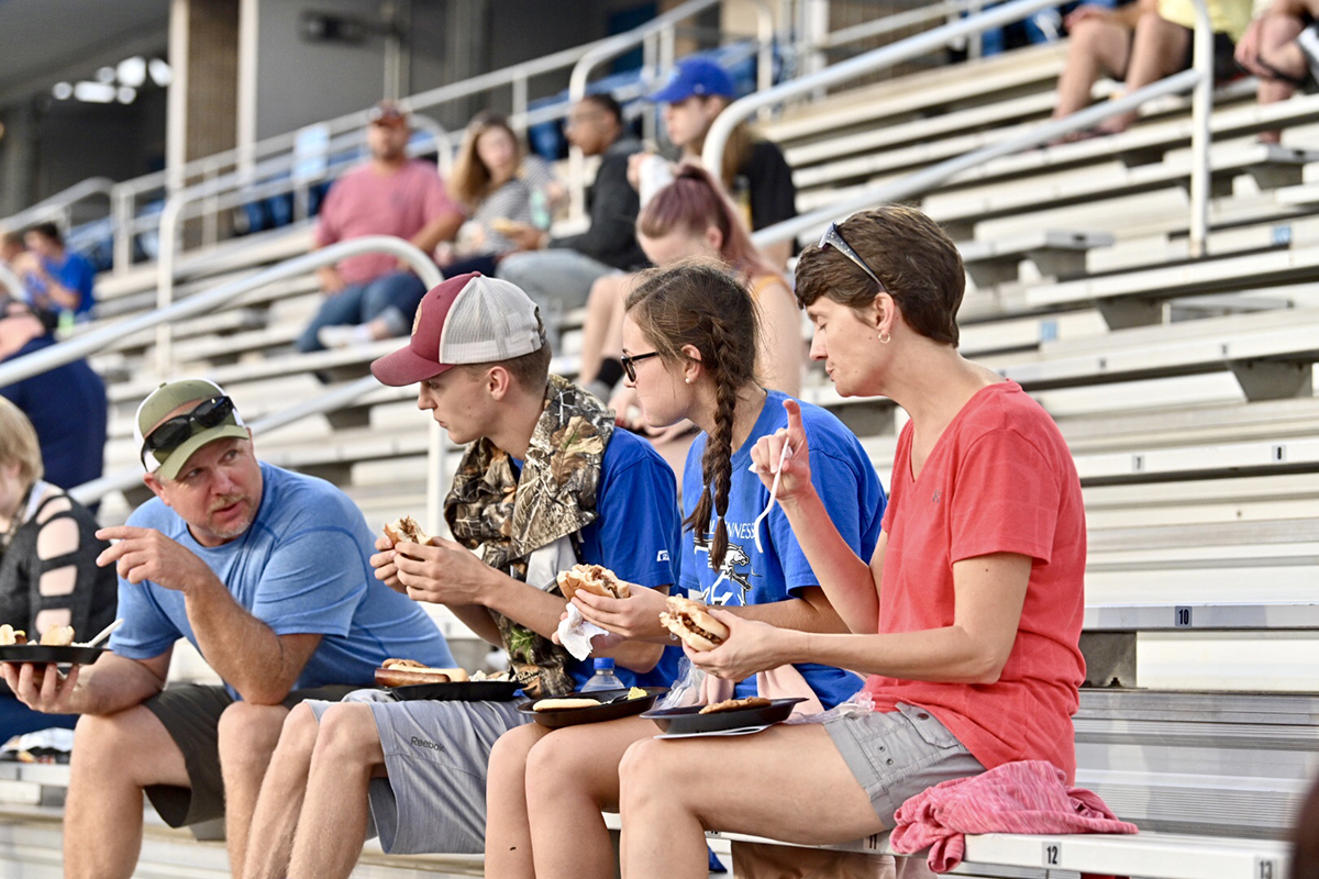 A family enjoys sitting in the Floyd Stadium stands eating food provided for the President's Picnic following University Convocation in Murphy Center Saturday, Aug. 24. (MTSU photo)