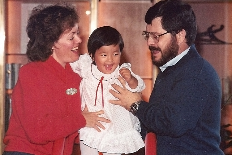 "MTSU language professor Bonnie Tinsley, left, and her husband, Cliff Richeson, hold their baby daughter, Pema, in a photo from Christmas 1986 in Hong Kong. Tinsley, a guest on the Aug. 27, 2019, edition of ""MTSU On the Record"" on WMOT-FM Roots Radio 89.5, wrote about their quest to adopt Pema from Mother Teresa's Missionaries of Charity orphanage in India in ""Against Every Hope: India, Mother Teresa, and a Baby Girl."" (Photo submitted)"