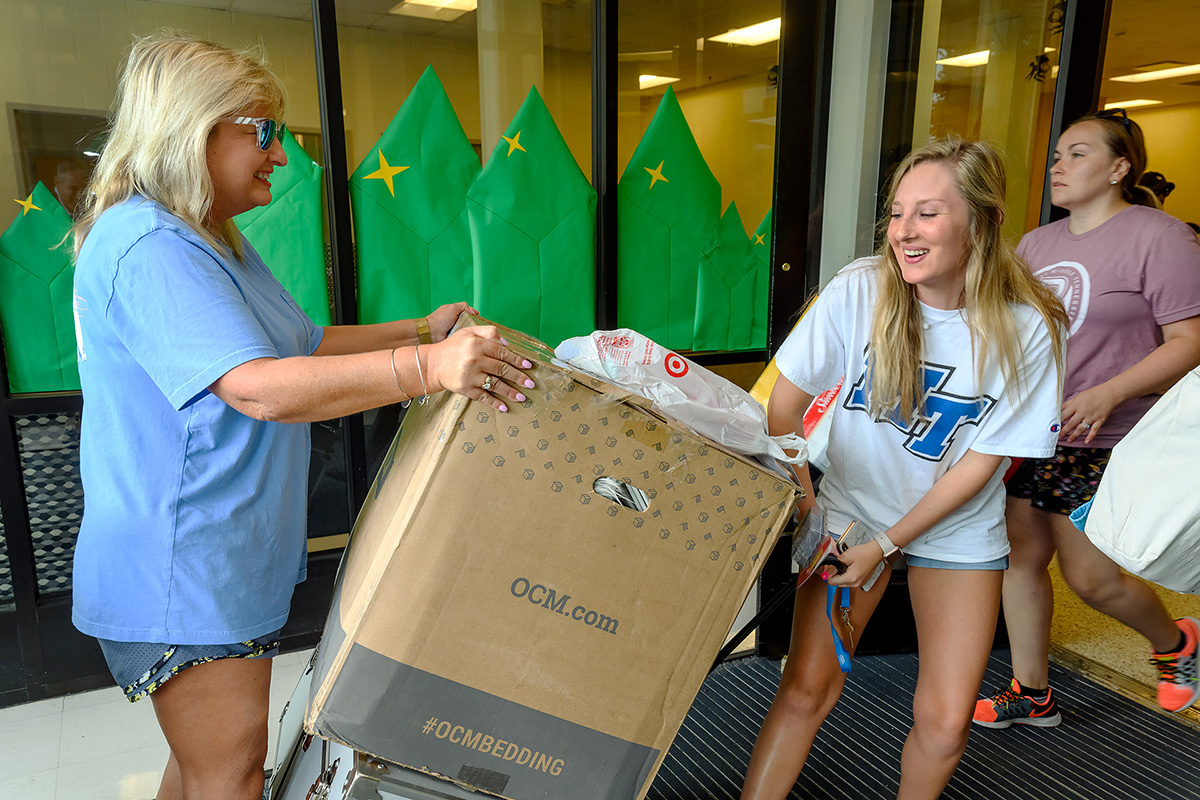 Madison Ratliff, 19, right, of Bristol, Tenn., and her mother, Sherry Ratliff, haul in a large box and chest as part of the new MTSU freshman's belongings being carried into Corlew Hall Friday, Aug. 23, as part of the MTSU Center for Student Leadership and Involvement's We-Haul move-in effort. Madison Ratliff is an early childhood education major. (MTSU photo by J. Intintoli)
