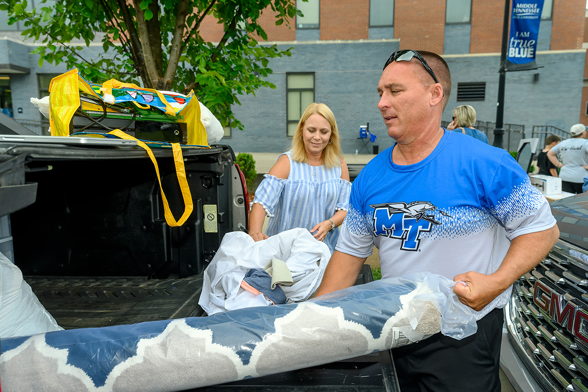 "Parents Brad Shelnutt, foreground right) and Meredith ""Rhea"" Howell, both from Locust Grove, Ga., move items off of a pickup truck as they help their respective sons move into Cummings Hall during We-Haul Friday, Aug. 23, at MTSU. Brandon Shelnutt and Cade Howell, both 18, will be aerospace professional pilot majors. (MTSU photo by J. Intintoli)"